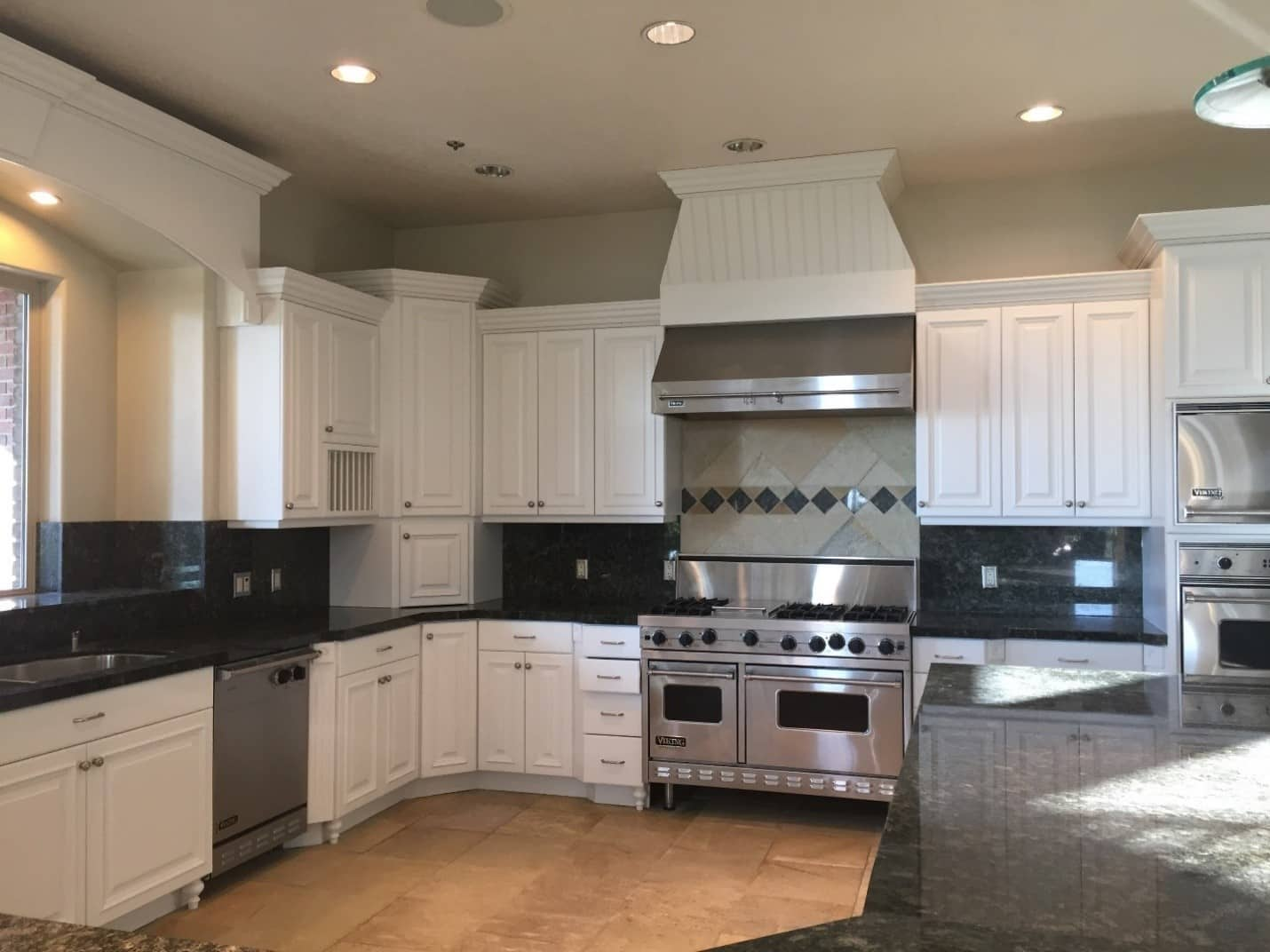 A stylish kitchen with stone countertops and newly painted drawers and cabinets
