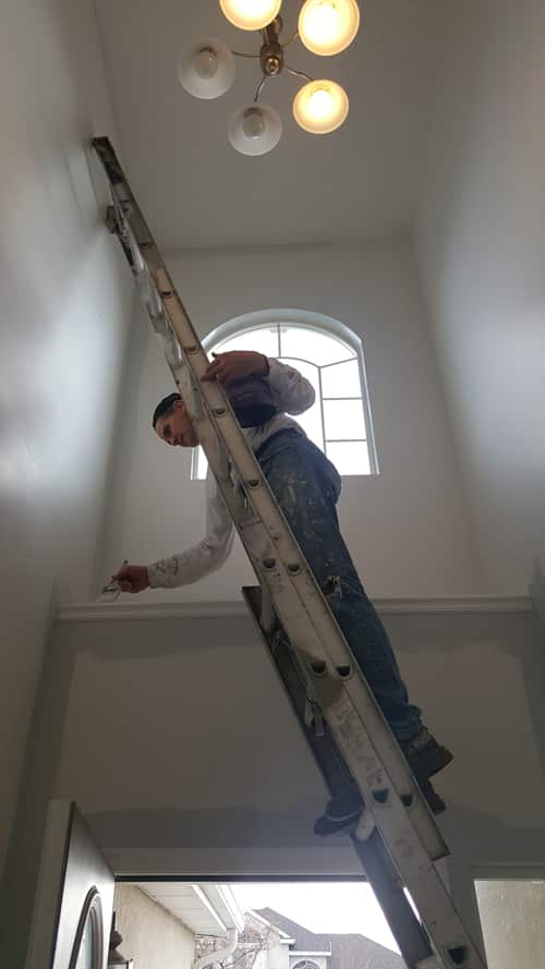 Painter on a ladder using a detailing brush to paint a ledge above the door