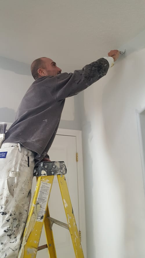 Man on a ladder who applies some primer to the ceiling before painting