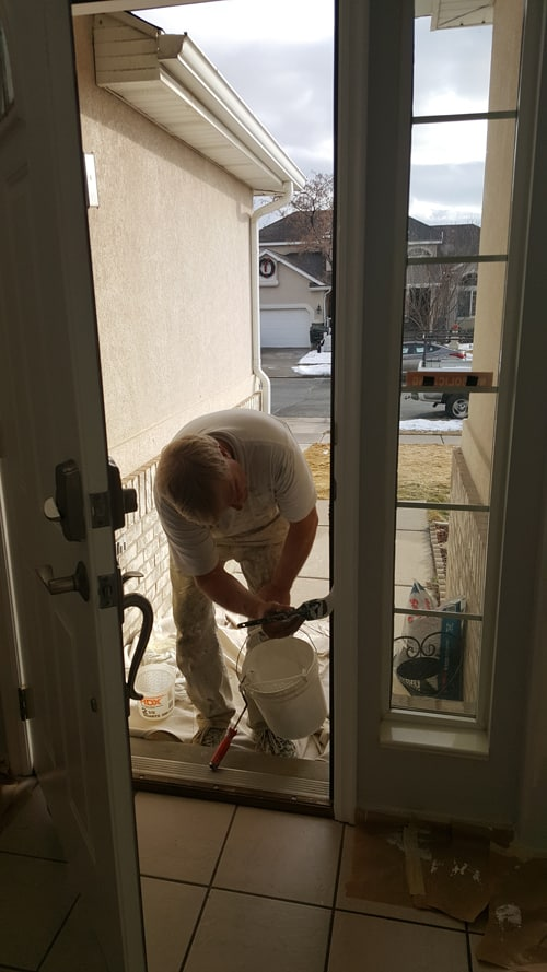 Residential painting job where a contractor carefully paints the door's edge white