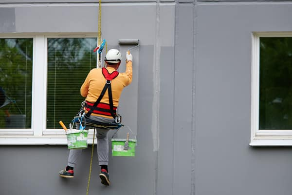 Painter on a contraption while painting the exterior of a tall building