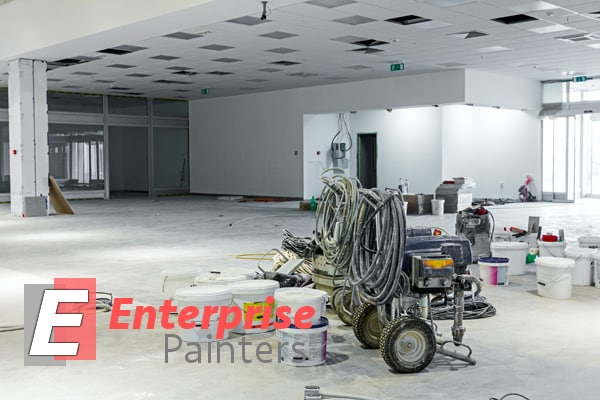 Wide shot of a commercial building interior undergoing a full-on paint job