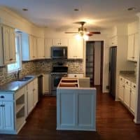 Kitchen cabinets, center isle, and hanging shelves freshly painted in white