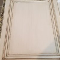 White wooden door of a kitchen cabinet that needs painting