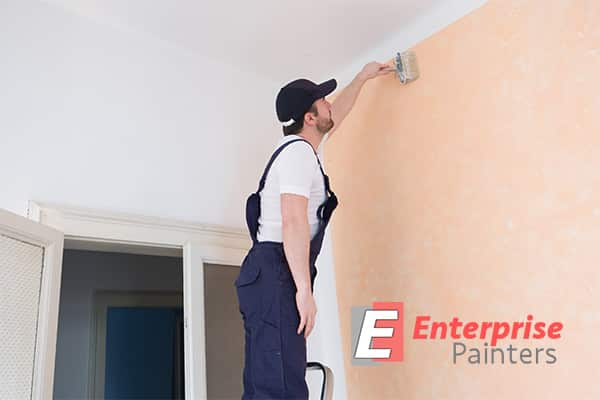 A professional painter on a ladder while coating the wall with peach paint