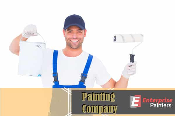 A smiling Enterprise Painters contractor holding a roller brush and paint bucket