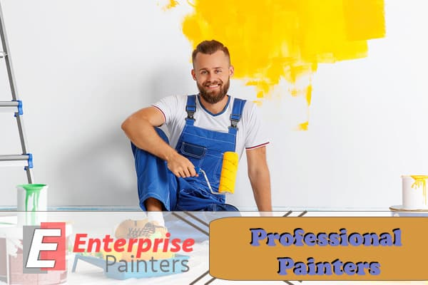 Professional painter of Enterprise Painters with a roller dipped in yellow paint