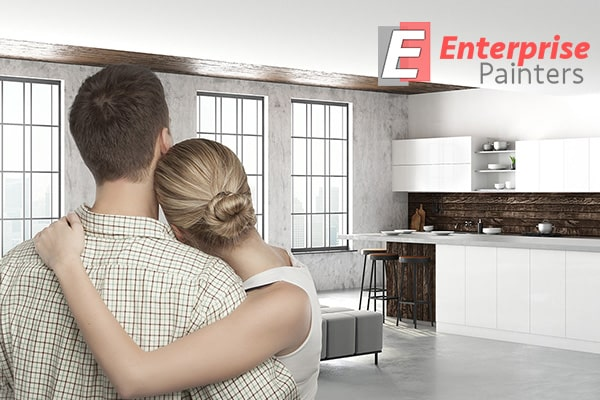 Over-the-shoulder shot of a couple, embracing and proud of a newly-painted home